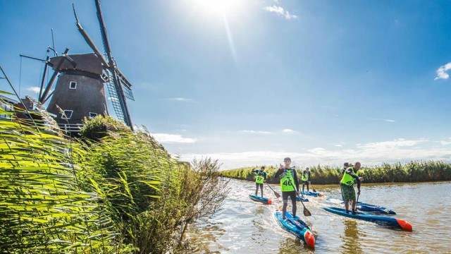 Daniel Hasulyo passes by a windmill in Friesland, The Netherlands during the 2017 SUP 11 City Tour