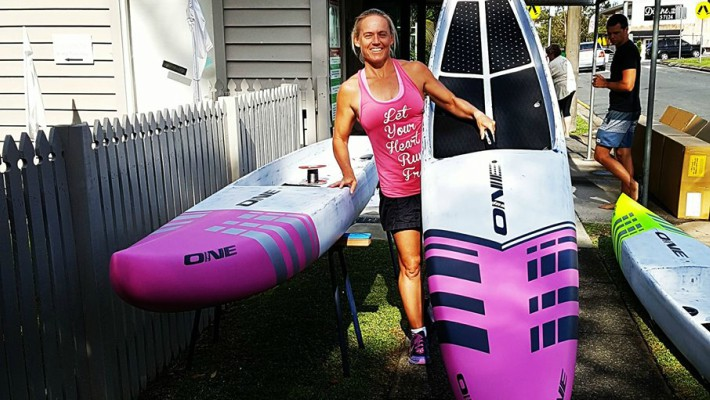 Angela Jackson poses in front if two boards from her very own brand ONE Stand Up Paddle