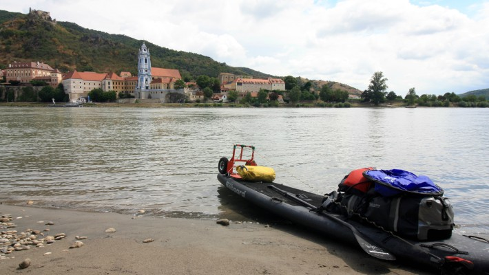 Mark Hines takes a breather with his BillboardSUP boards by another riverside village in Bulgaria