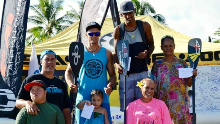 Niuhiti-Nui Buillard sur la première place du podium entouré de concurrents et d'amis