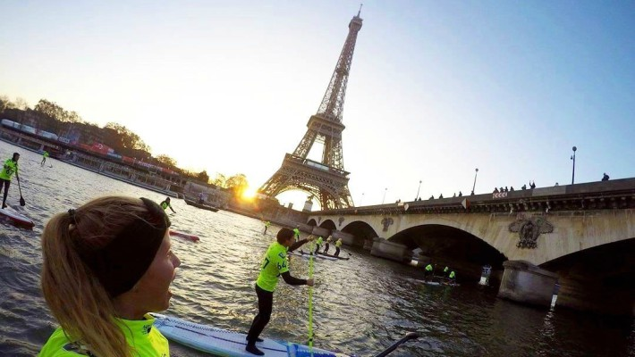 Competitors admire the view as they pass by the Eiffel Tower at the 2016 edition of the Nautic SUP Paris Crossing