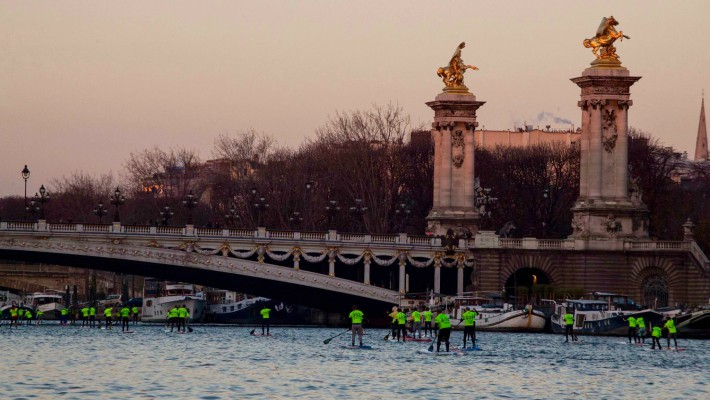 Paddlers race past the ornate Alexandre III bridge in Paris