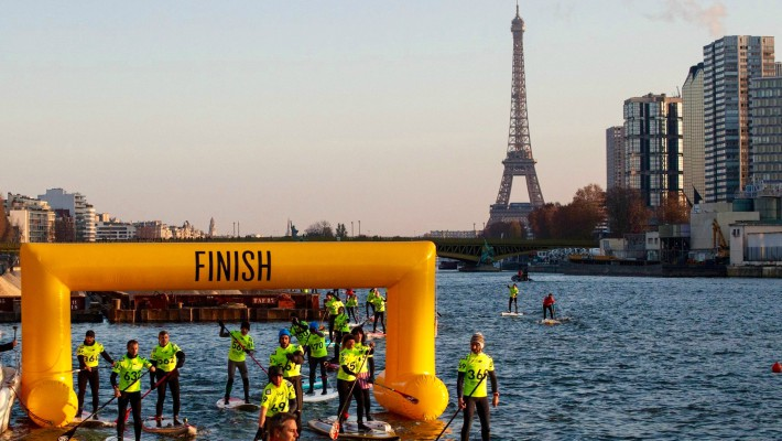 Paddlers cross the finish line at Beaugrenelle with the Eiffel Tower in the background at the 2016 edition of the Nautic SUP Paris Crossing