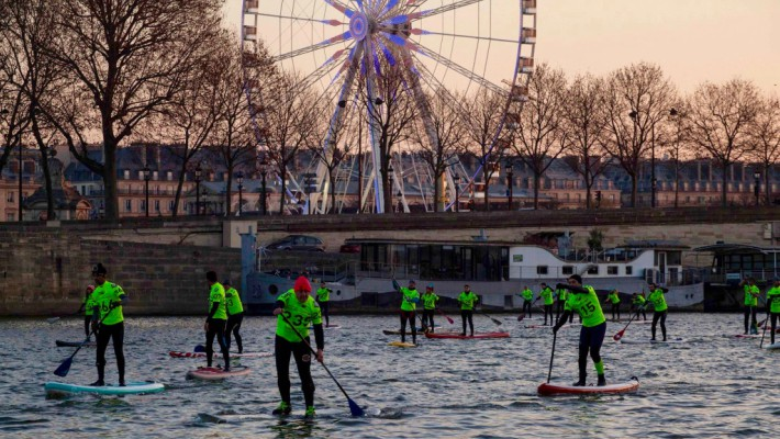 Participating paddlers pass by the quays by the Tuileries gardens in central Paris at the 2016 Nautic SUP Paris Crossing