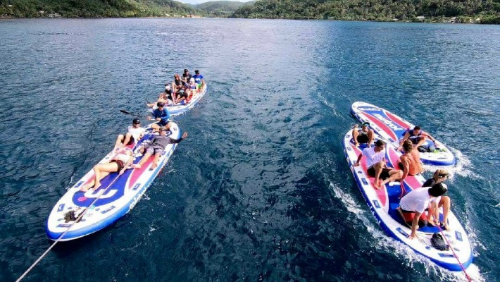 Multi-person SUP boards ferry participants of the 2017 Ironmana in Huahine, French Polynesia
