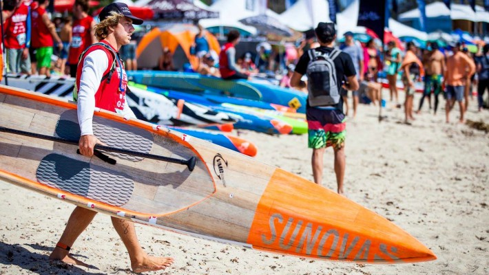 James Casey walks with his Sunova board to the shore, ready to take off at another Australia-based SUP event