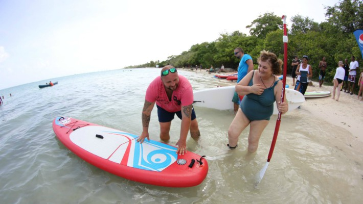 Philippe Momparler assists a new paddler at the inauguration of his O Lagon paddling and watersports equipment service in Saint-Martin